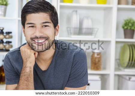 Portrait of handsome smiling young Asian man with a beard in a kitchen at home - stock photo