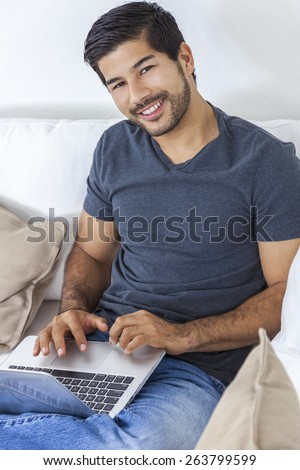 Portrait of handsome smiling young Asian man with a beard using laptop computer at home - stock photo