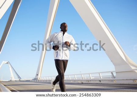 Portrait of handsome sporty man enjoying a run outdoors working out against blue sky background  - stock photo