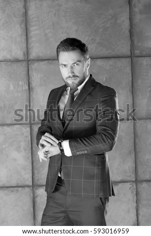 Portrait of handsome stylish bearded young man in elegant blue suit with vest and tie, perfect hair style checking time on watch. Black and white