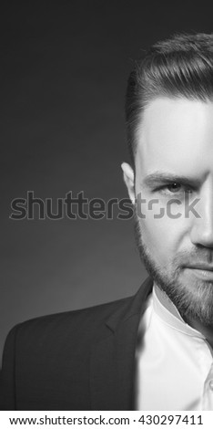 Portrait of handsome stylish caucasian bearded young man in elegant blue suit and white shirt with perfect hair style. Black and white