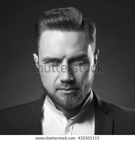 Portrait of handsome stylish caucasian bearded young man in elegant blue suit and white shirt with perfect hair style give a wink on camera. Black and white - stock photo