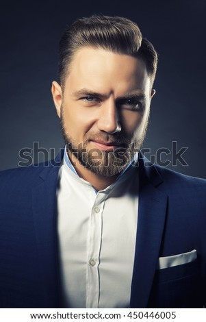 Portrait of handsome stylish caucasian bearded young man in elegant blue suit and white shirt with perfect hair style smiling when looking at camera. Toned - stock photo