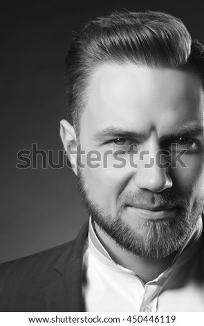 Portrait of handsome stylish caucasian bearded young man in elegant blue suit and white shirt with perfect hair style smiling when looking at camera. Black and white - stock photo