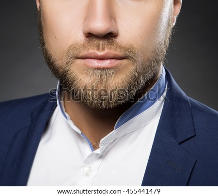 Portrait of handsome stylish caucasian bearded young man in elegant blue suit and white shirt with perfect hair style looking at camera. T - stock photo