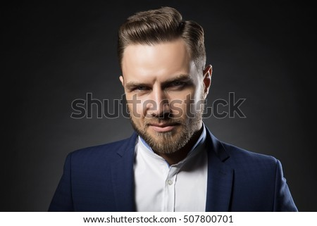 Portrait of handsome stylish caucasian bearded young man in elegant blue suit and white shirt with perfect hair style smiling when looking at camera.
