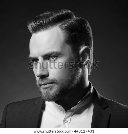 Portrait of handsome stylish caucasian young man in elegant blue suit with perfect hair style. Black and white - stock photo