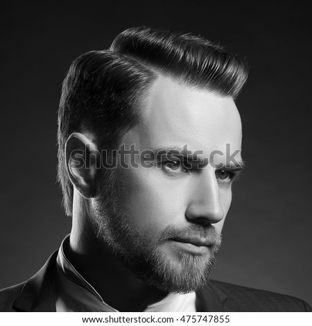 Portrait of handsome stylish caucasian young man in elegant blue suit with perfect hair style. Black and white.