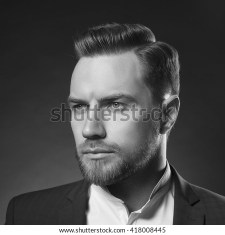 Portrait of handsome stylish caucasian young man in elegant blue suit with perfect hair style. On gradient grey background. Black and white. - stock photo