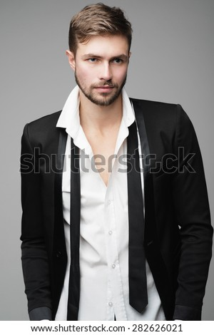 Portrait of handsome stylish man in a suit in the studio - stock photo