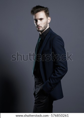 Portrait of handsome stylish man in elegant black suit. Young beautiful man in black tie. Beautiful male wear. Man with stylish haircut. Modern fashion. Elegant men's style. New fashionable look.