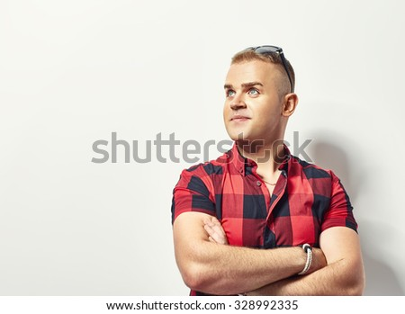 Portrait of handsome stylish man in plaid shirt and sunglasses with copy space - stock photo