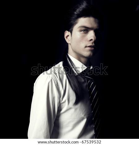 Portrait of handsome stylish men looking out of the darkness - stock photo