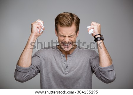 Portrait of handsome stylish young man on grey background. Angry man crumpling paper with his eyes closed