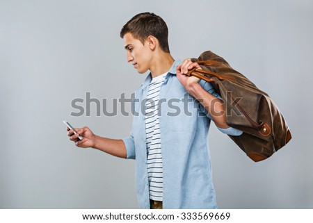 Portrait of handsome stylish young man standing on grey background. Man with bag wearing shirt and using mobile phone - stock photo