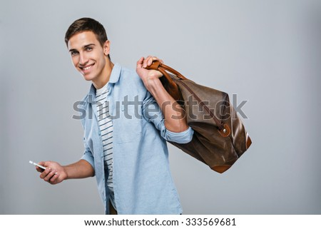 Portrait of handsome stylish young man standing on grey background. Smiling man with bag wearing shirt, using mobile phone and looking at camera - stock photo