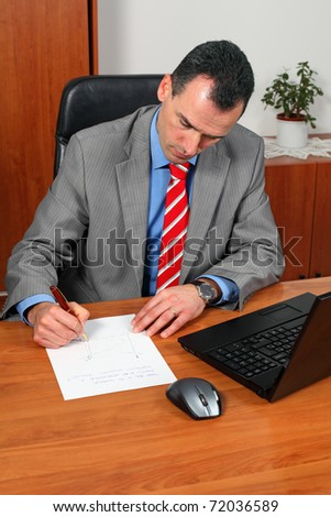 Portrait of handsome successful businessman in his office