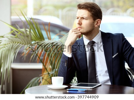 Portrait of handsome successful man drink coffee and look to the digital tablet screen sitting in coffee shop, business man having breakfast  - stock photo