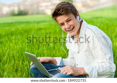 Portrait of handsome teen student working on laptop in green grass field.