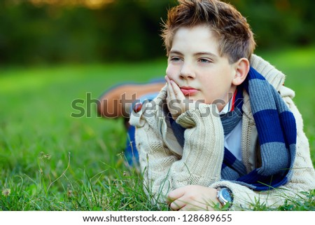portrait of handsome teenager on green grass - stock photo