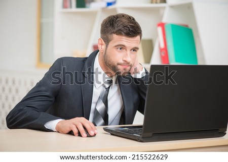 Portrait of handsome tired businessman sitting at the table attentively working looking at laptop with tension on his face and touching his neck in office background