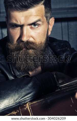 Portrait of handsome unshaven male biker in black leather jacket sitting in garage with big brown old briefcase looking forward on workshop background, vertical picture - stock photo