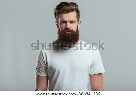 Portrait of handsome young bearded man looking at camera while standing against gray background - stock photo