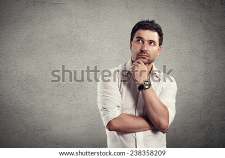 Portrait of handsome young business man having creative idea. Conceptual shoot of Caucasian brunette standing at grey wall. - stock photo
