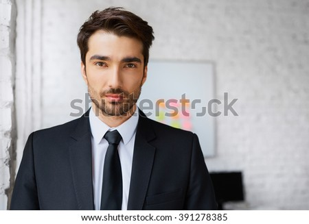 Portrait of handsome young business man standing in office - stock photo