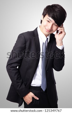 Portrait of handsome young business man using cell phone, smiling isolated on gray background, asian model