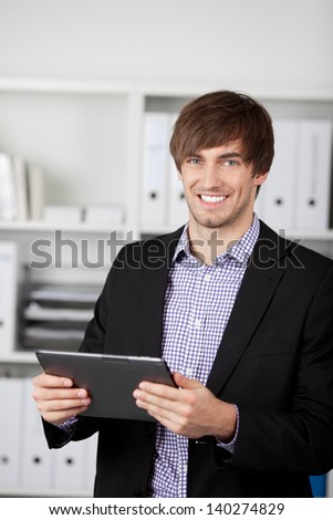 Portrait of handsome young businessman holding digital tablet in office - stock photo