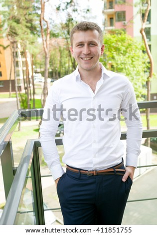 Portrait of handsome young businessman posing on balcony - stock photo