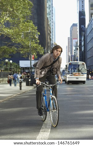 Portrait of handsome young businessman riding bicycle on urban street - stock photo