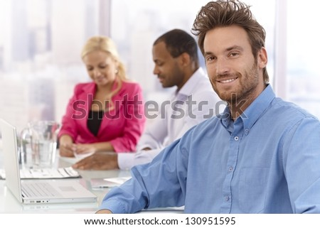 Portrait of handsome young businessman sitting at a meeting, smiling confident.