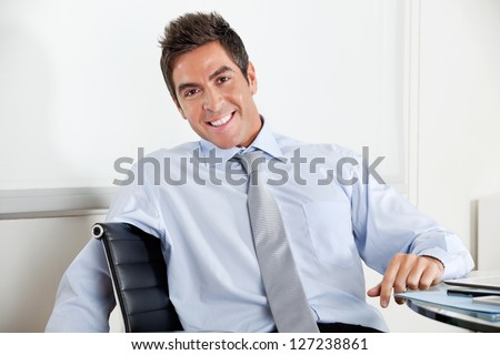 Portrait of handsome young businessman smiling at desk in office - stock photo
