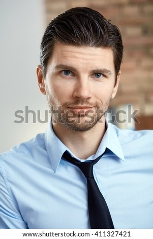 Portrait of handsome young businessman smiling, looking at camera. - stock photo