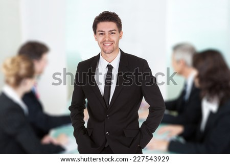 Portrait of handsome young businessman standing against colleagues in meeting at office - stock photo