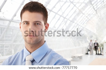 Portrait of handsome young businessman standing in office lobby.? - stock photo