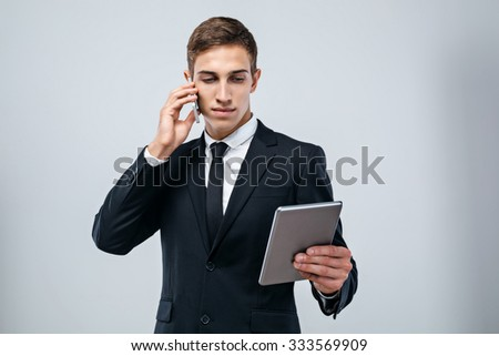 Portrait of handsome young businessman standing on grey background. Businessman wearing suit and tie, holding tablet computer and talking on phone