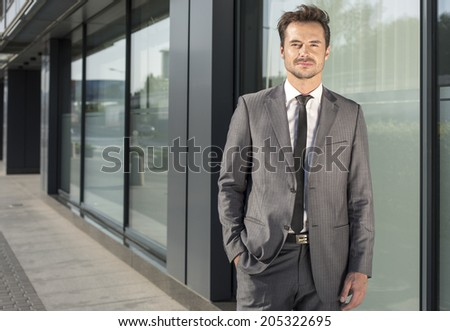 Portrait of handsome young businessman standing outside office building - stock photo