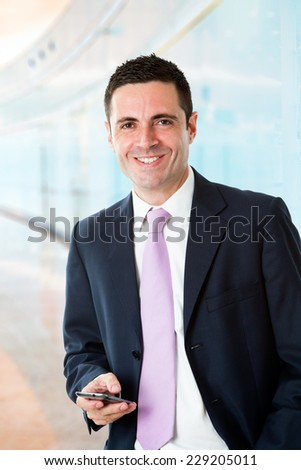Portrait of Handsome young businessman standing with smart phone at work. - stock photo