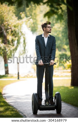 Portrait of handsome young businessman wearing suit. Man using segway and looking aside. Green alley as background - stock photo