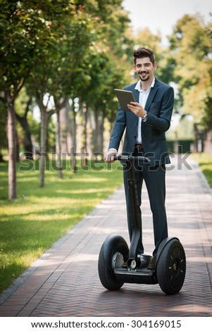 Portrait of handsome young businessman wearing suit. Man using segway and tablet computer. Man smiling and looking at camera. Green alley as background - stock photo
