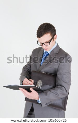 Portrait of handsome young businessman with notebook and briefcase - stock photo