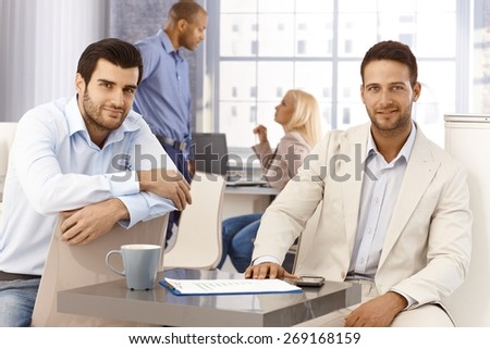 Portrait of handsome young businessmen sitting by table, looking at camera, smiling. - stock photo