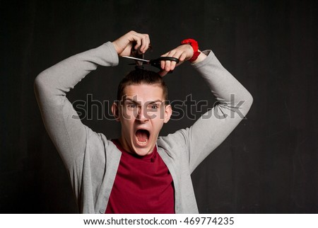 Portrait of handsome young dark-haired man cutting hair with scissors and shouting. Isolated on black background