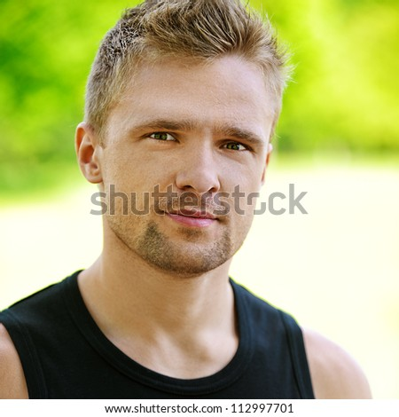 Portrait of handsome young dressed in black man, against green of summer park.