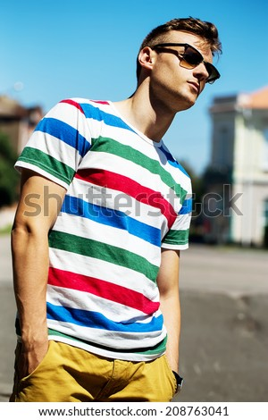 Portrait of handsome young fashionable man  in sunglasses on the - stock photo