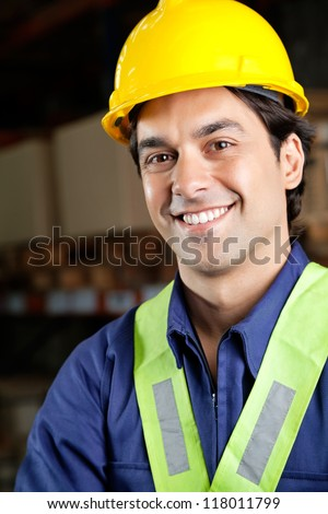 Portrait of handsome young foreman with yellow hardhat smiling at warehouse - stock photo