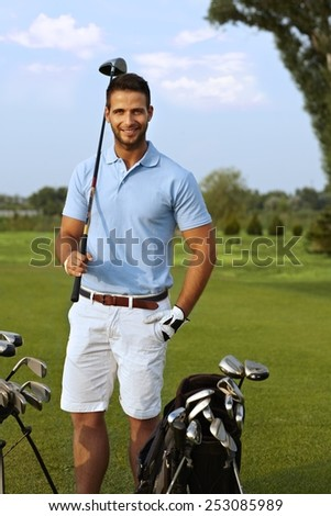 Portrait of handsome young golfer holding golf club, smiling, looking at camera. - stock photo